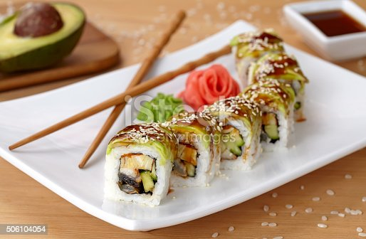 Green dragon sushi roll with eel, avocado, cucumber, wasabi and ginger. Traditional asian rice sushi healthy seafood. White plate, wooden table background.