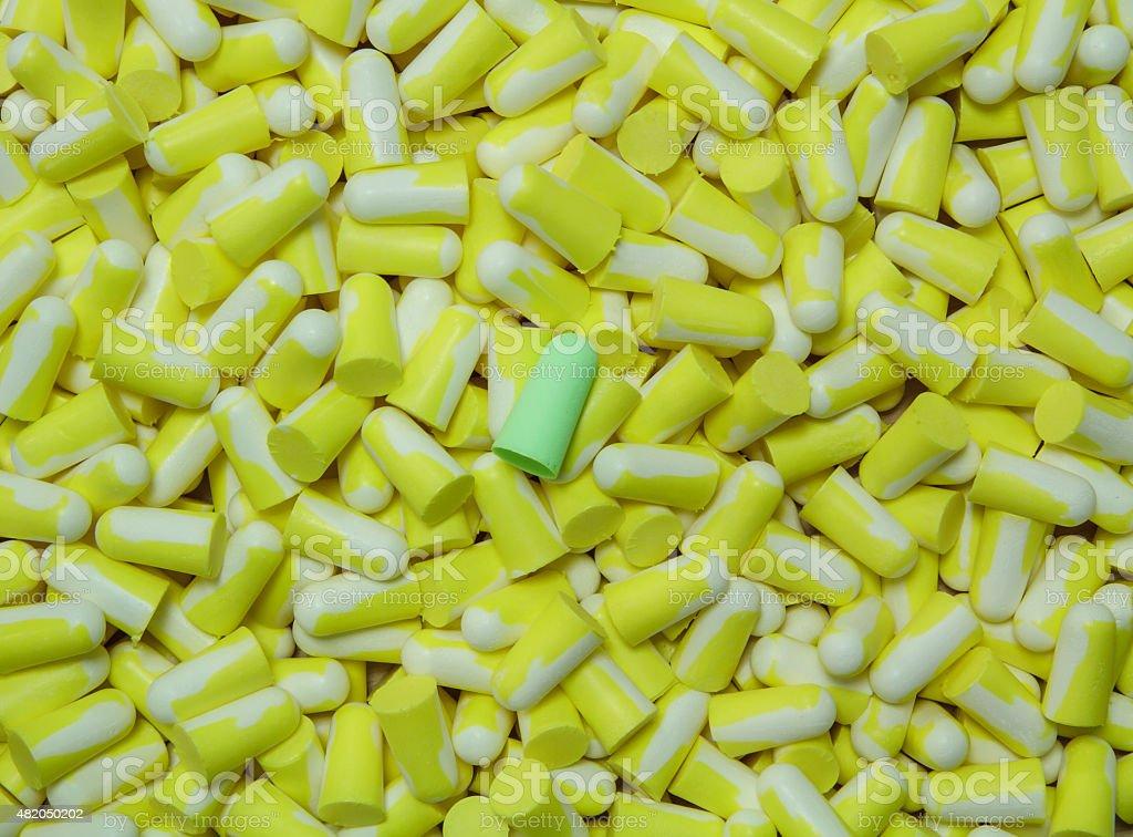 Green ear plug on the several yellow ear plug. stock photo
