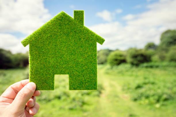 vert respectueux de l'environnement de maison en arrière-plan - écologiste rôle social photos et images de collection