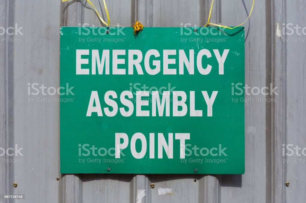 Green Emergency Assembly Point Sign Mounted To A Metal Construction