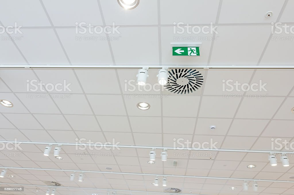 Green emergency exit sign on ceiling, modern light. stock photo