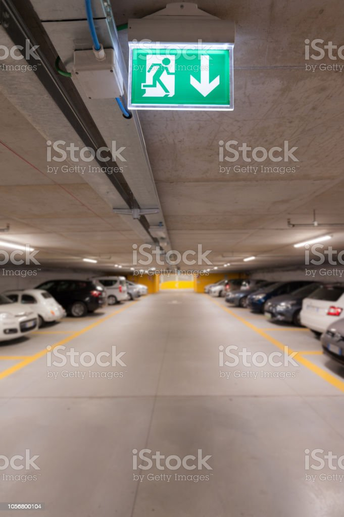 Green emergency exit sign on white in the parking car. image for...