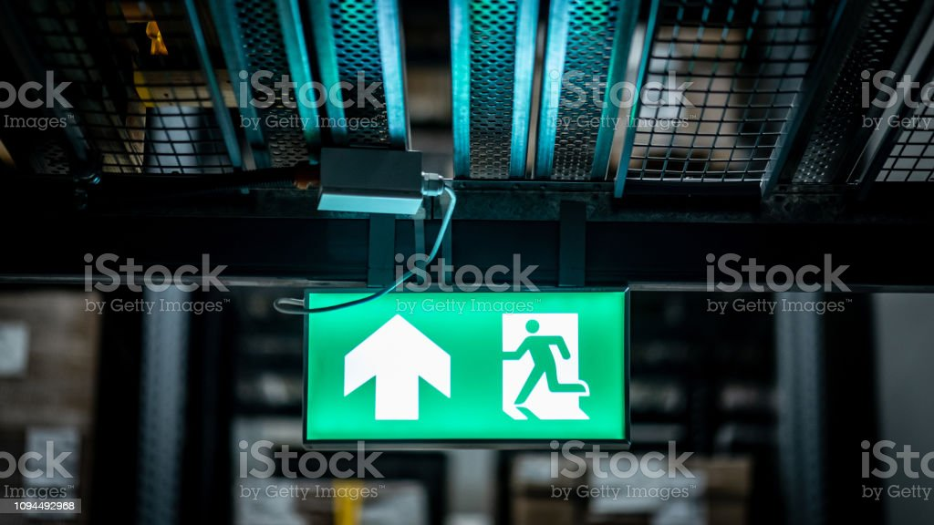Green emergency exit sign or fire exit sign showing the way to escape...