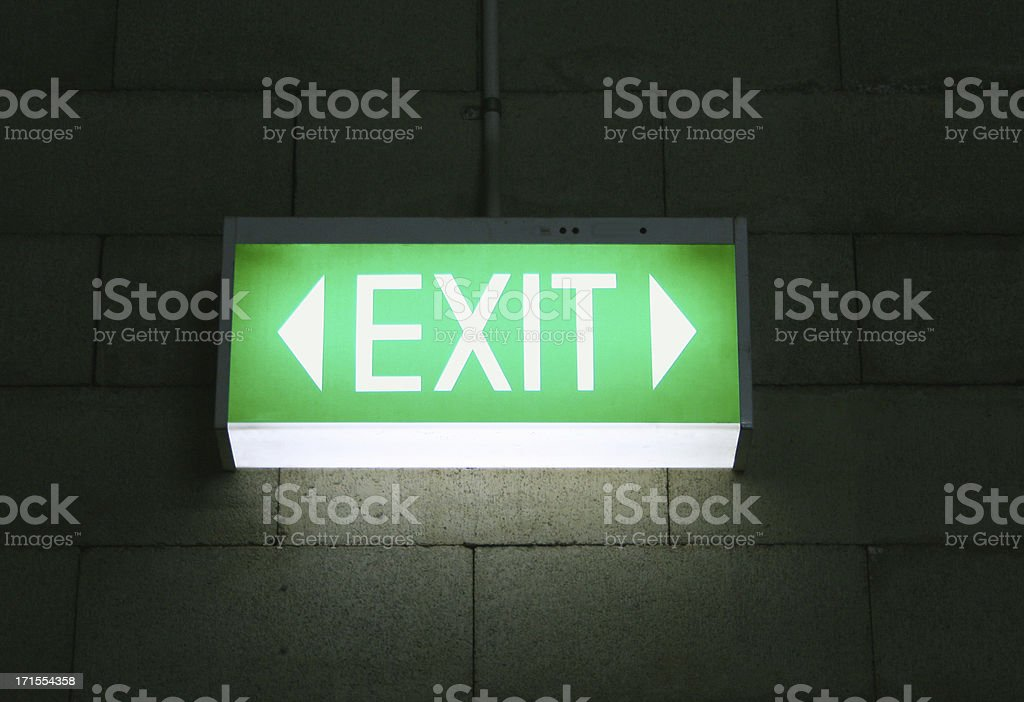 A green emergency exit sign found in an office.