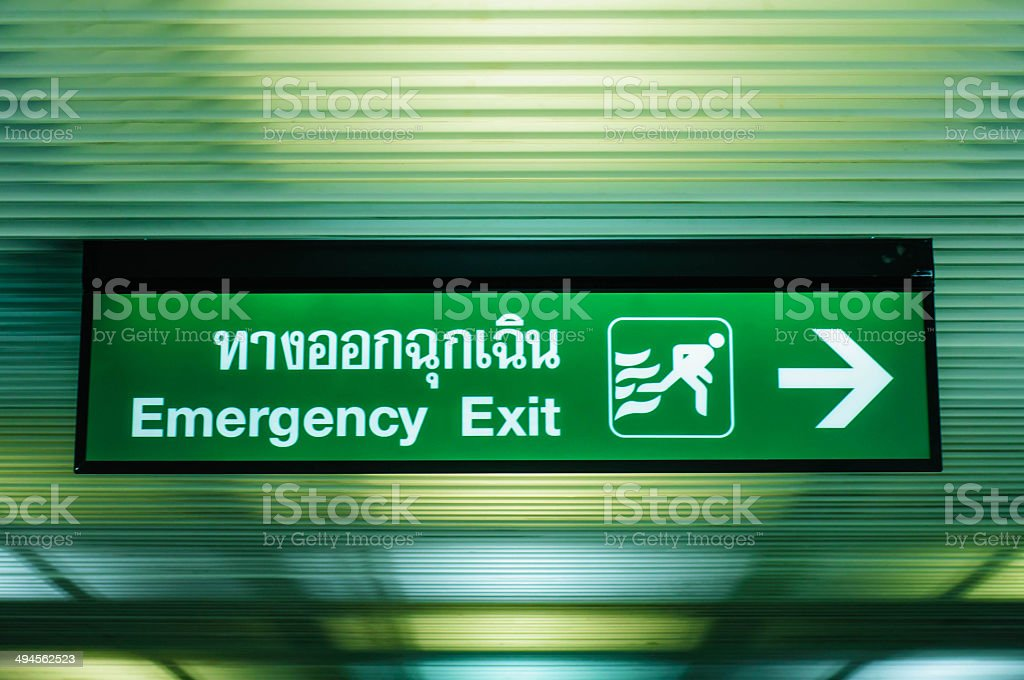 Green emergency exit sign at the airport terminal