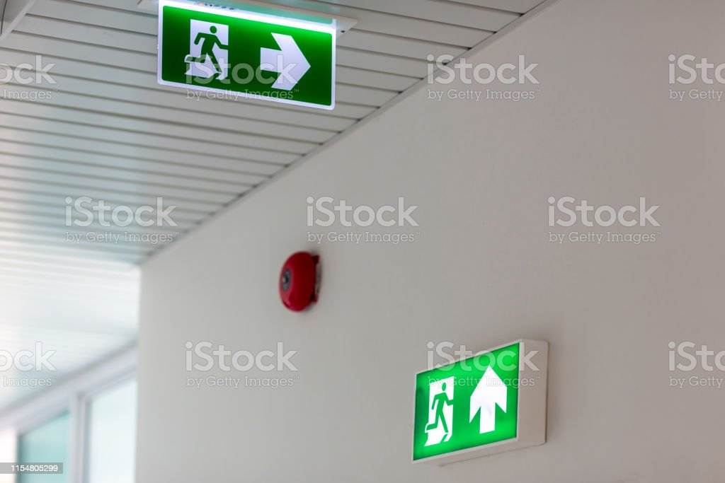 Green emergency exit sign showing the way to escape.Fire exit in the...