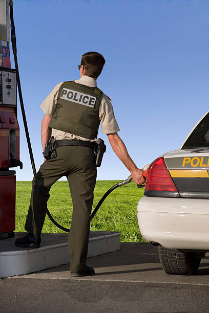 Green energy Policeman filling up his cruiser at the gas station. trooper stock pictures, royalty-free photos & images