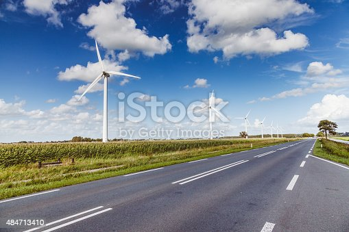istock Green energy - Wind turbines and a dutch road 484713410