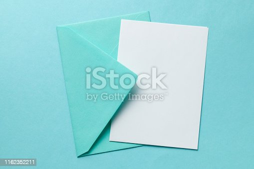 Green envelope and blank letter on green background. Template with place for text on postcard. mock-up.