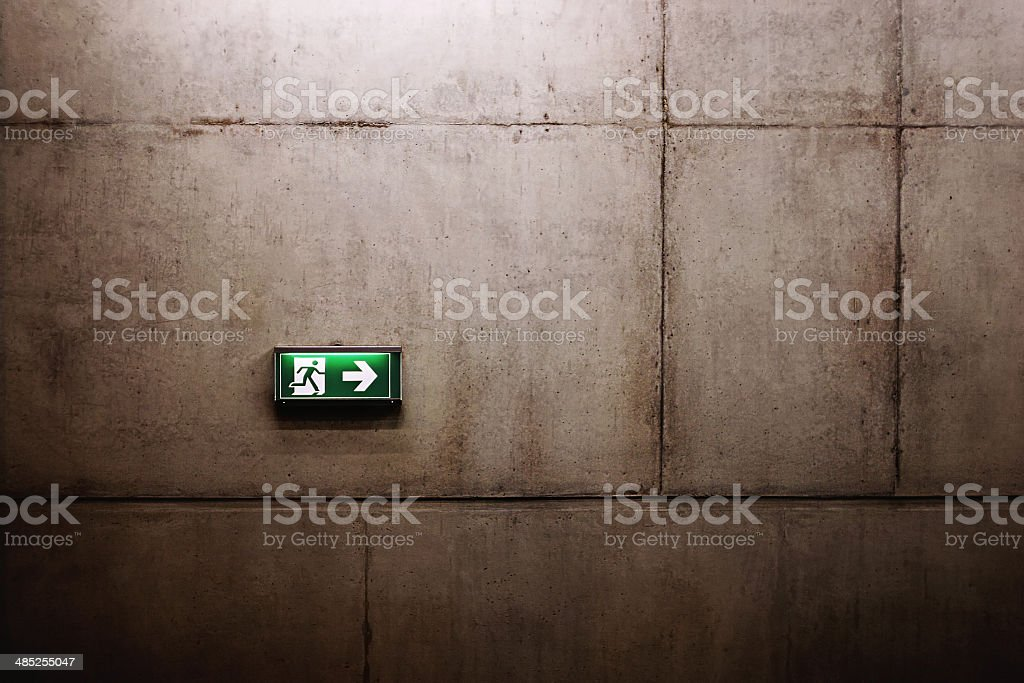 green exit sign on the wall stock photo
