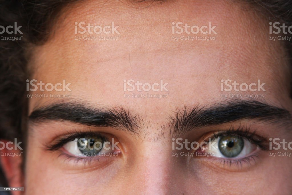 Green eyes of young man looking at you stock photo