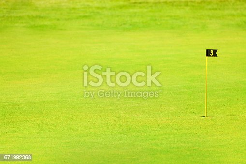 Green fairway of golf course with pin or flagstick and cup
