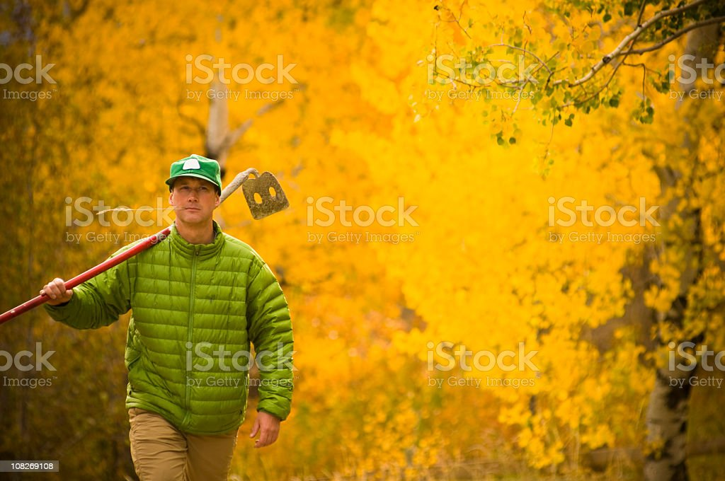 Green Farmer with a hoe walking in autumn stock photo