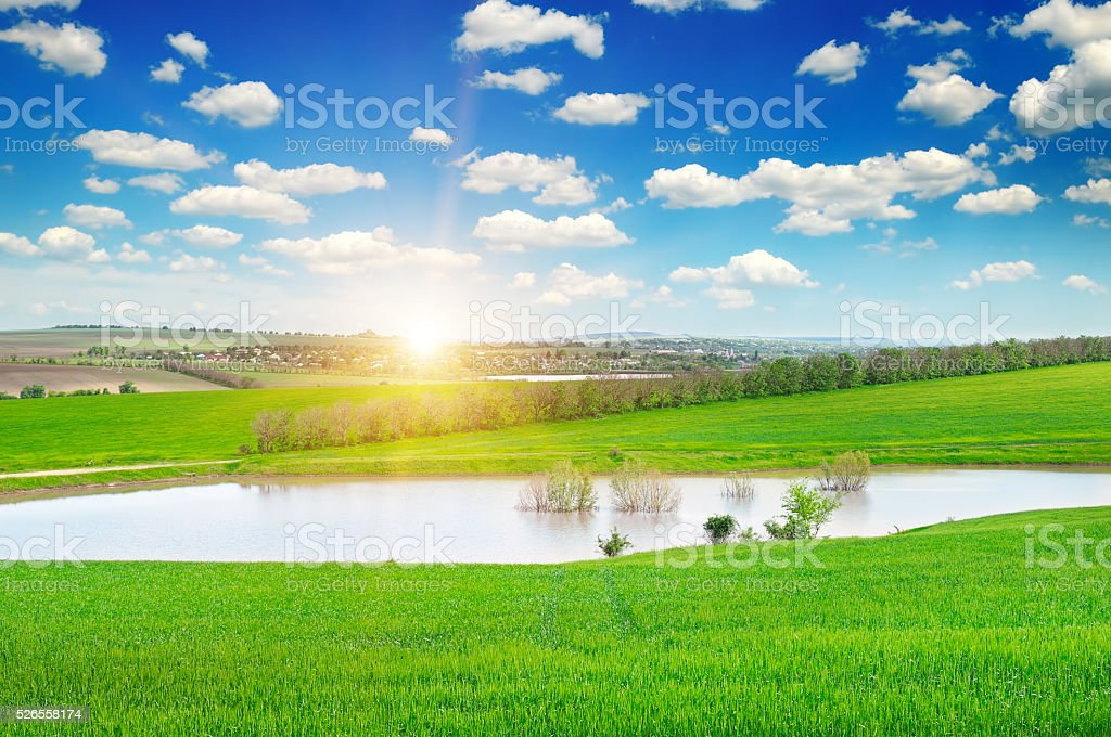 green field, lake and sunrise stock photo
