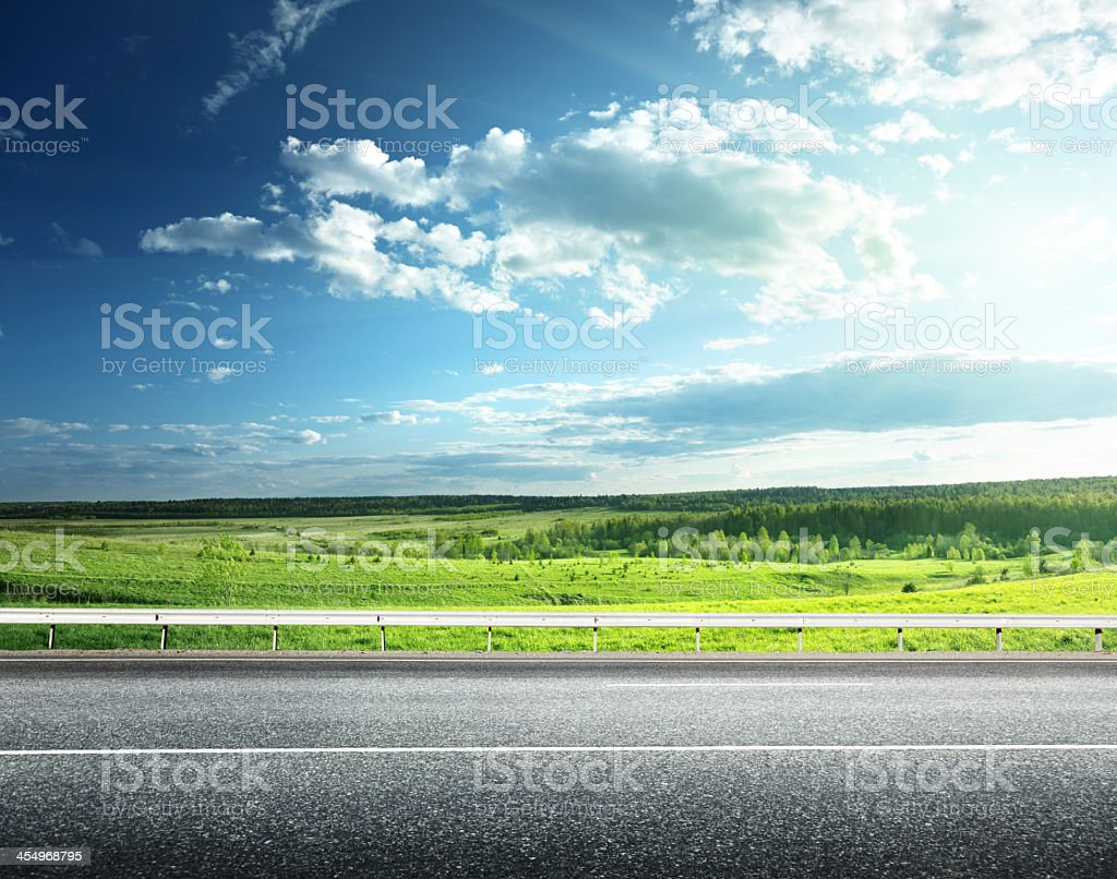 Green field next to an asphalt road stock photo