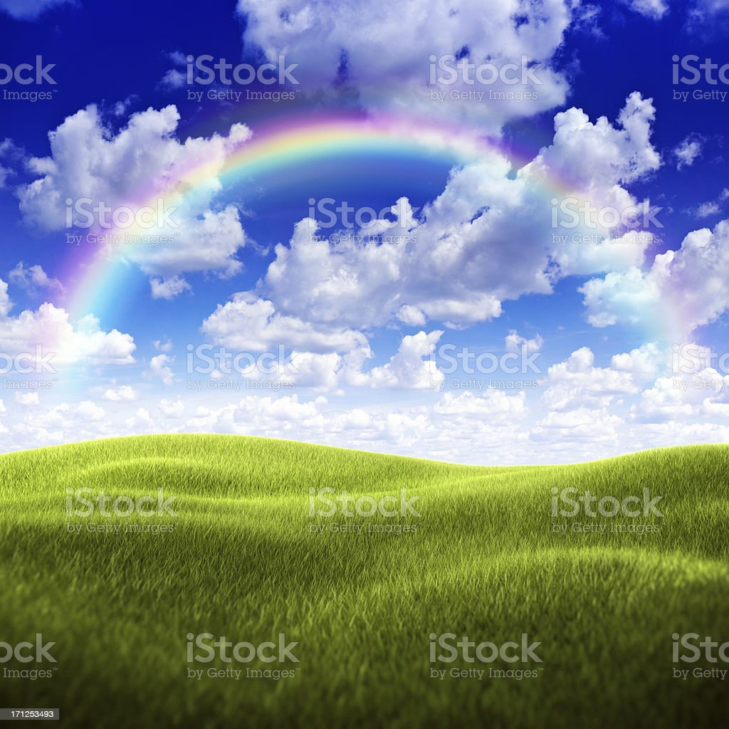 Green field over moody sky and rainbow stock photo