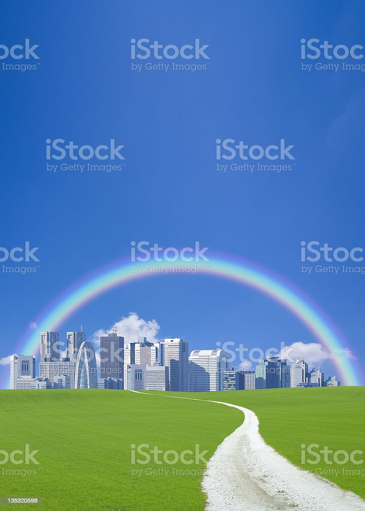 Green field with city covered by a rainbow royalty-free stock photo