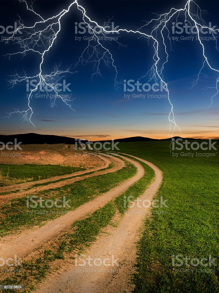 green field with storm dark clouds stock photo