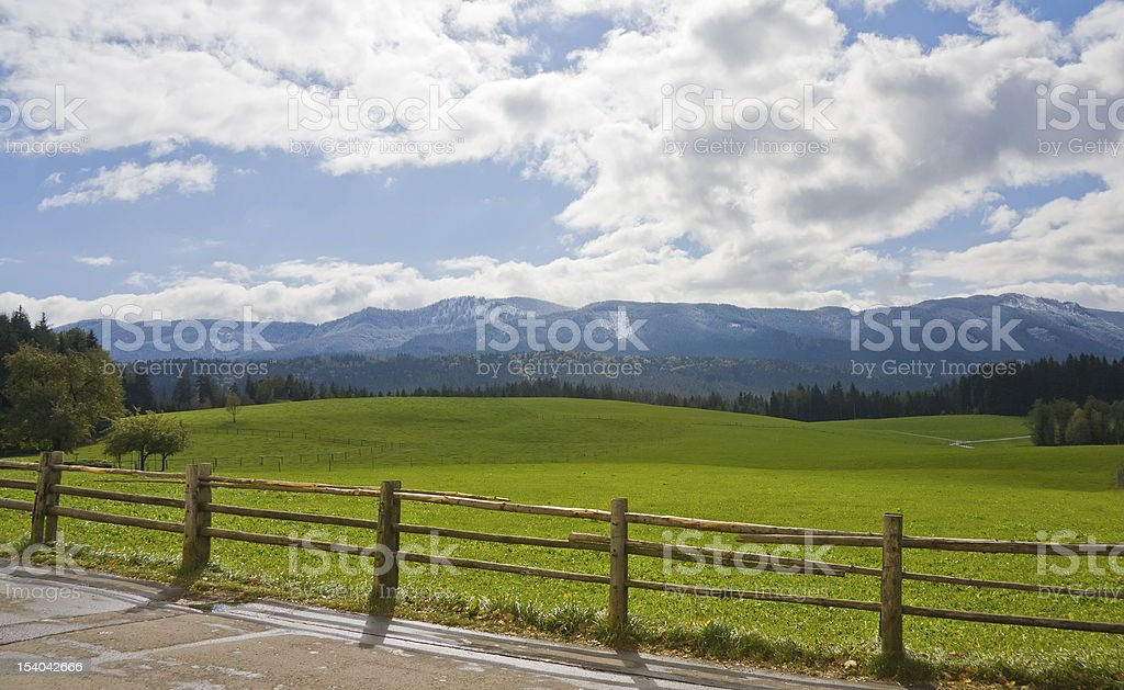 Green field with wooden fence in Bavarian Alps, Germany royalty-free stock photo