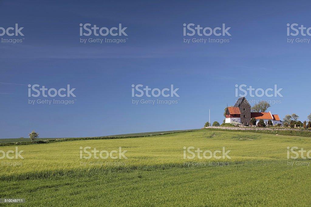 Green fields by the Ruts Kirke church on Bornholm stock photo
