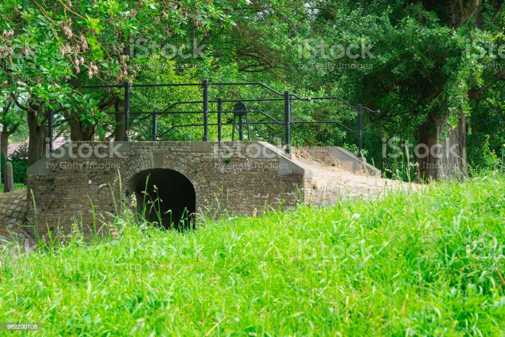 green filed and brick sluice bridge in Klundert, The Netherlands stock photo