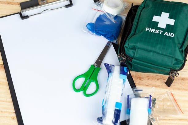 Green first aid kit on a table with a clipboard Green first aid kit on a wooden table with a clipboard and a pair of scissors and some dressings first aid stock pictures, royalty-free photos & images