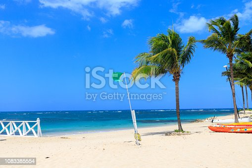 Green flag on the beach indicates no danger when bathing. Dominican Republic.