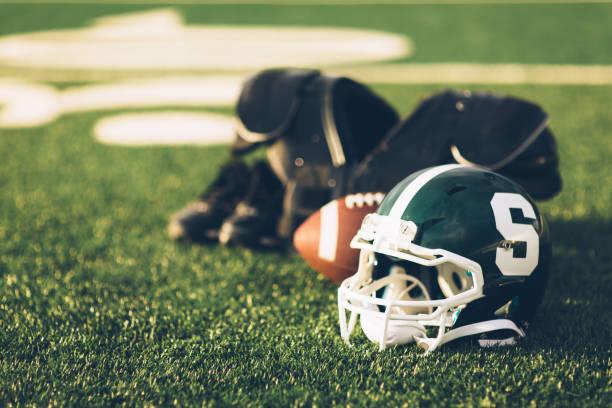 casque de football vert sur champ - ncaa photos et images de collection
