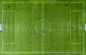 Aerial view of Green football pitch with unrecognizable little player silhouettes; outdoors.
