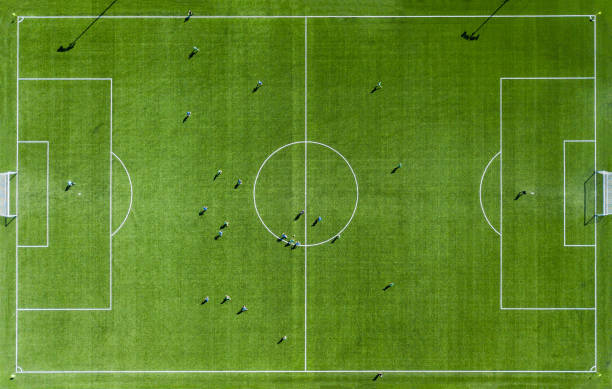 Green football pitch Aerial View Aerial view of Green football pitch with unrecognizable little player silhouettes; outdoors. soccer field stock pictures, royalty-free photos & images