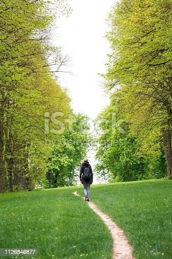 Young woman walking along footpath in Parc de Saint Cloud in Paris.