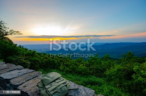 Green backpack on stone rock with sunset, mountains, and valley in the background