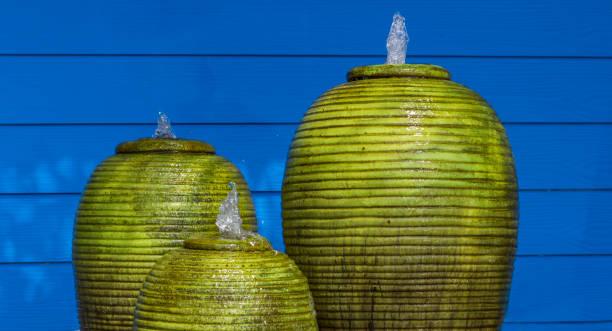 grüner brunnen jar und blaue wände friedliche - indoor wasserbrunnen stock-fotos und bilder