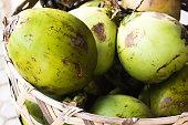 Green Fresh Coconuts in Woven Basket.