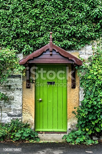 View of a green front door in an old cottage.