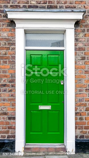 Chester, UK - January 27, 2016: View of a green front door set in brickwork with a white canopy.  There are no people in the photograph.
