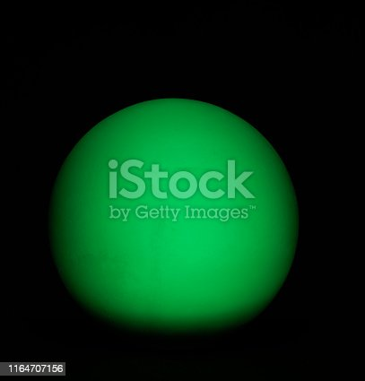 899255516 istock photo Green full sphere in the darkness 1164707156