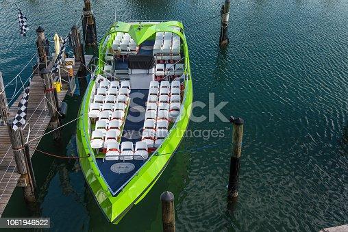 Green speed boat in a quiet harbor marina.