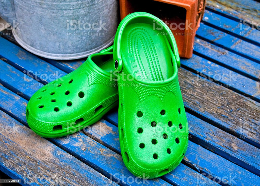 Green Garden Clogs On A Blue Table stock photo