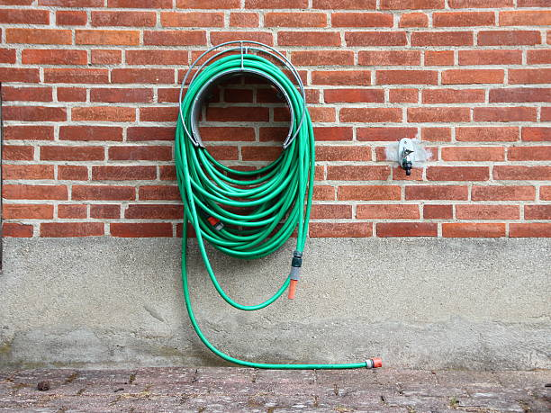 Green Garden Water Hose mounted on Red Brickwall Green Garden Water Hose Hanging on Red Brickwall. Not connected to Water Tap. hose stock pictures, royalty-free photos & images