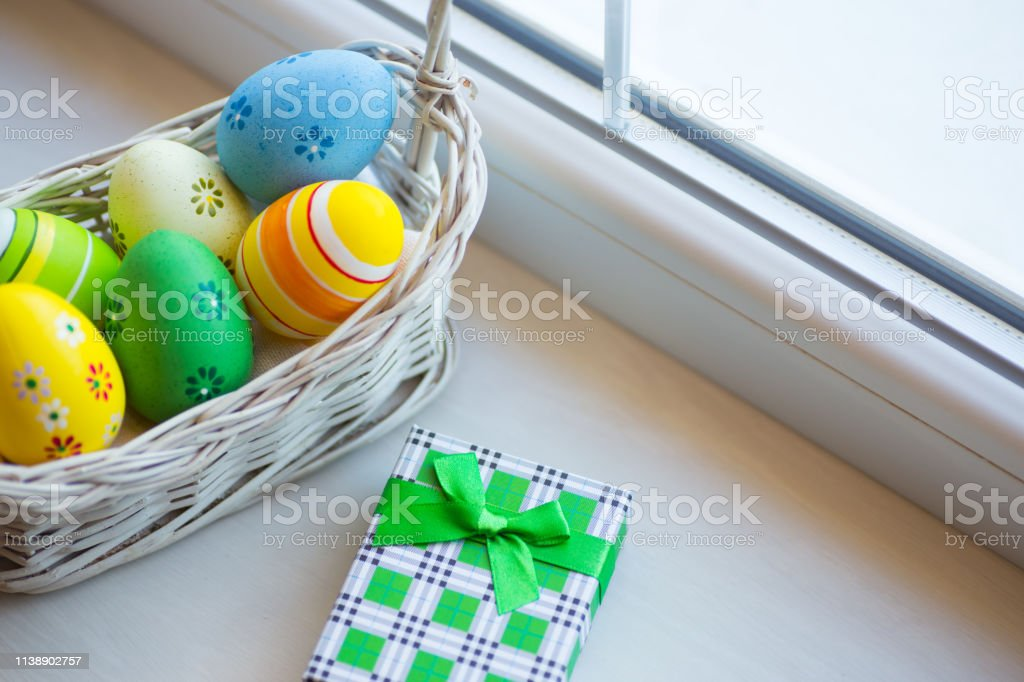 Green gift box and set of decorated colorful Easter eggs in wicker basket near window in daylight. stock photo