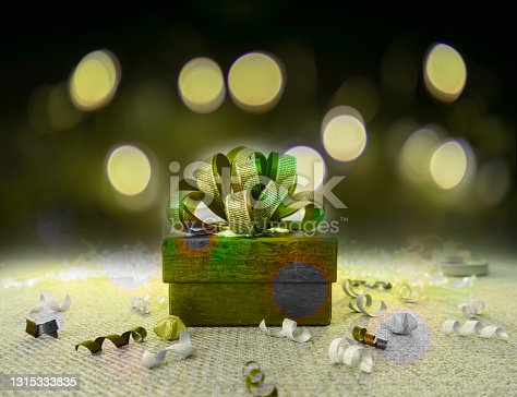 istock A green gift box with golden ribbon for celebrate Christmas and happy new year  on green fabric, under bokeh yellow lighting on dark background 1315333835