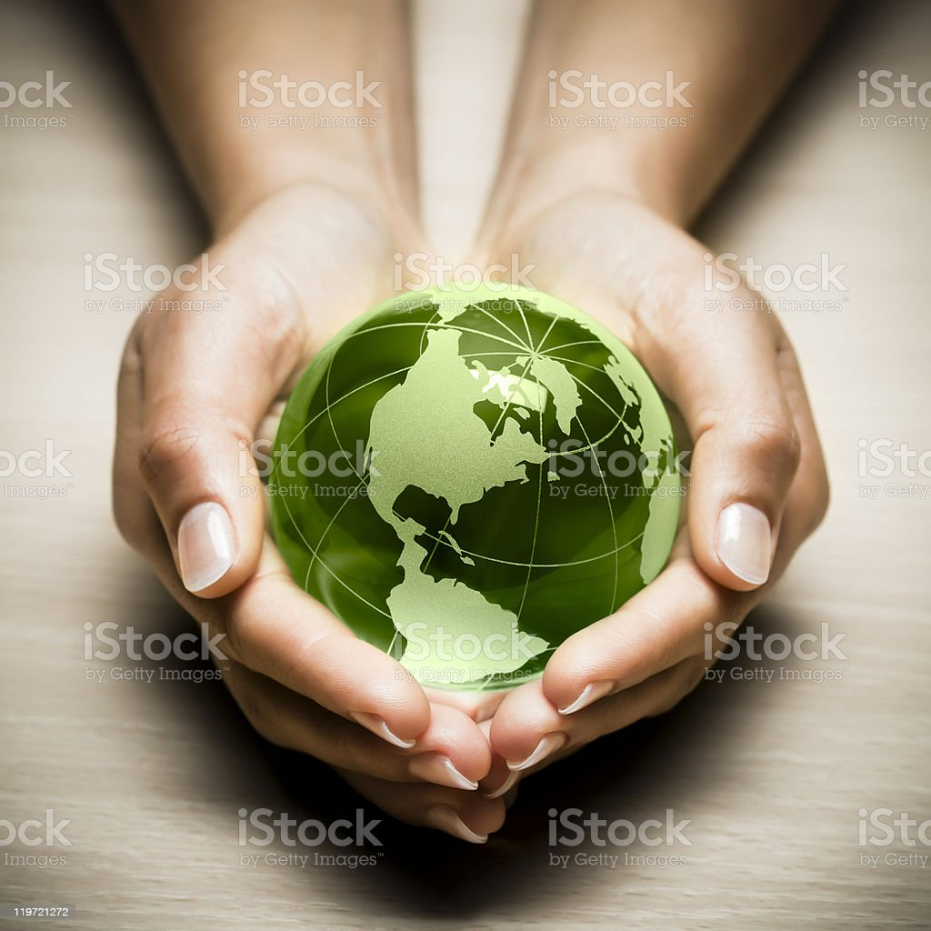 Green glass globe being held in hands royalty-free stock photo