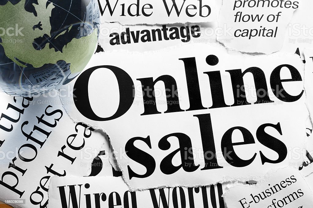 Green glass globe on headlines about online sales and trading royalty-free stock photo