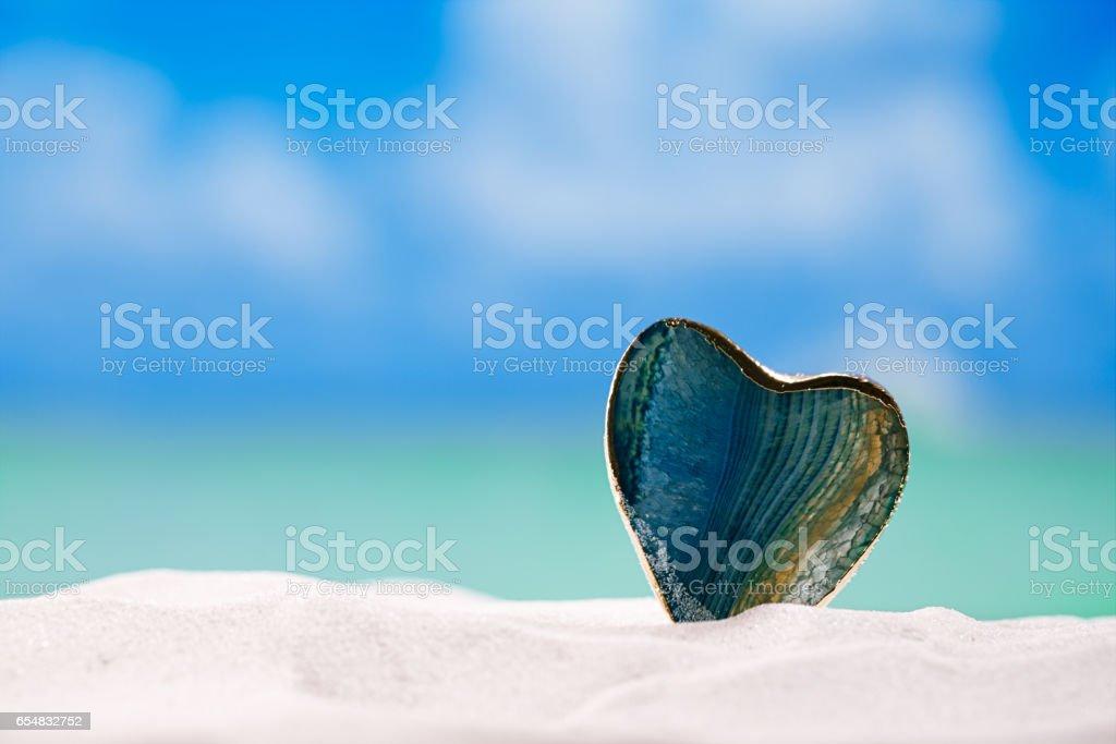 green glass heart on white sand beach, stock photo