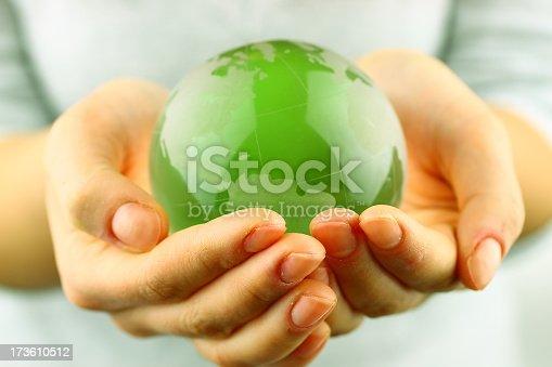 Green globe in hands
