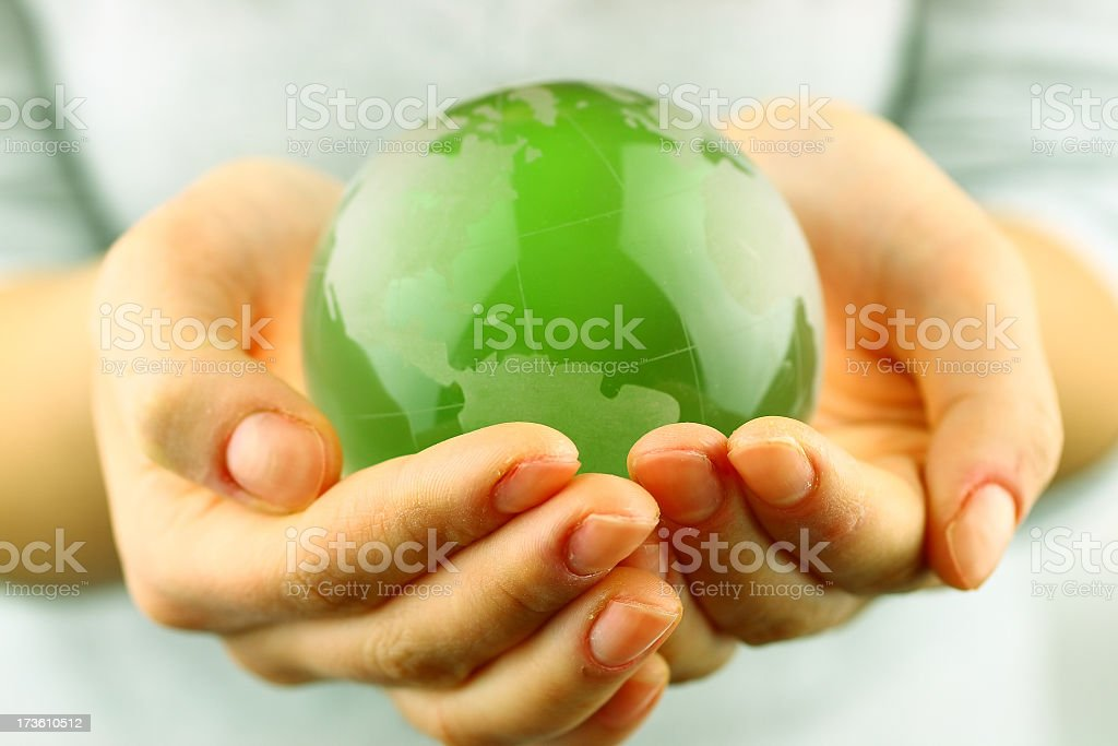 Green globe being held by a person's hands stock photo