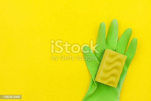 istock Green glove and a yellow sponge for cleaning on a yellow background. 1262973457