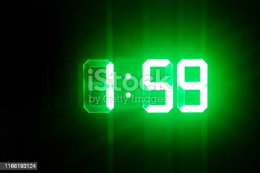 istock Green glowing digital clocks in the dark show 1:59 time 1166193124