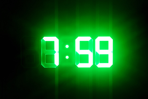 istock Green glowing digital clocks in the dark show 7:59 time 1165684746